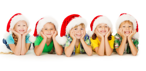 Christmas kids lying down and smiling in Santa red hat. Group of five children over white background